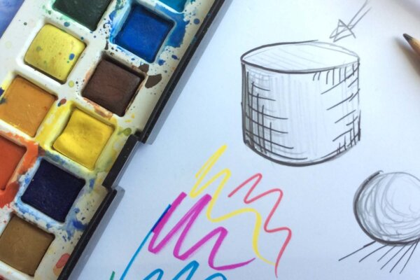 A tray of multicoloured paints sits next to a white canvas, where some shapes have been drawn on in pencil.