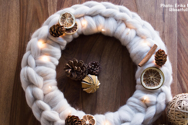 A circular wool wreath with pine cone and dried orange decoration