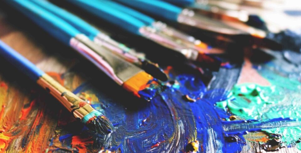 A close up angled shot of a variety of paintbrushes with paint on them, laid out on top of a painted canvas.