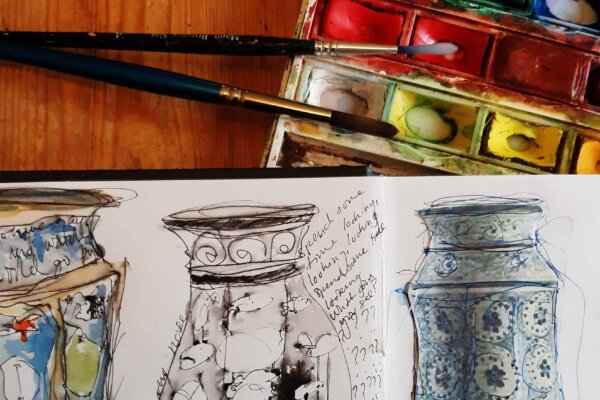 A watercolour painting set with two paint brushes and a open sketch book with sketches of different styles.