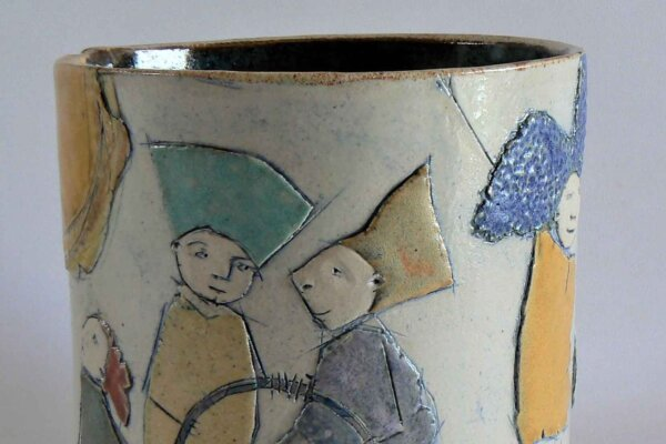 A clay pot with cartoonistic characters embossed on it.