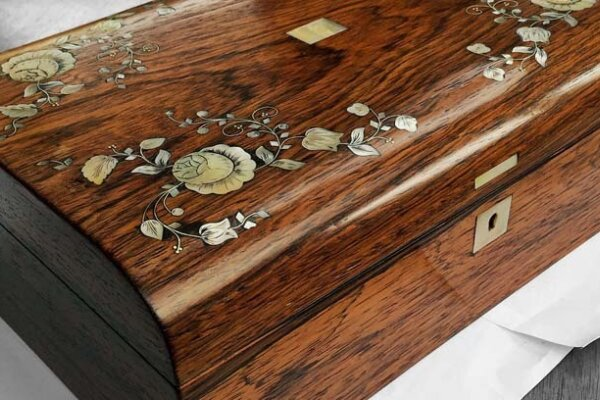 A polished wooden jewellery box with floral detail engraved on the lid.