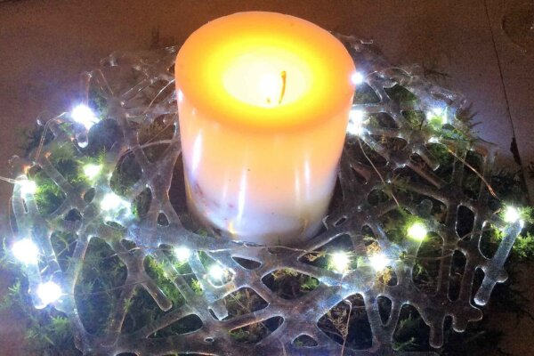 A candle surrounded at its base by a lattice glass wreath with entwined fairy lights.