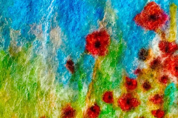 A needle felting of a field with poppies