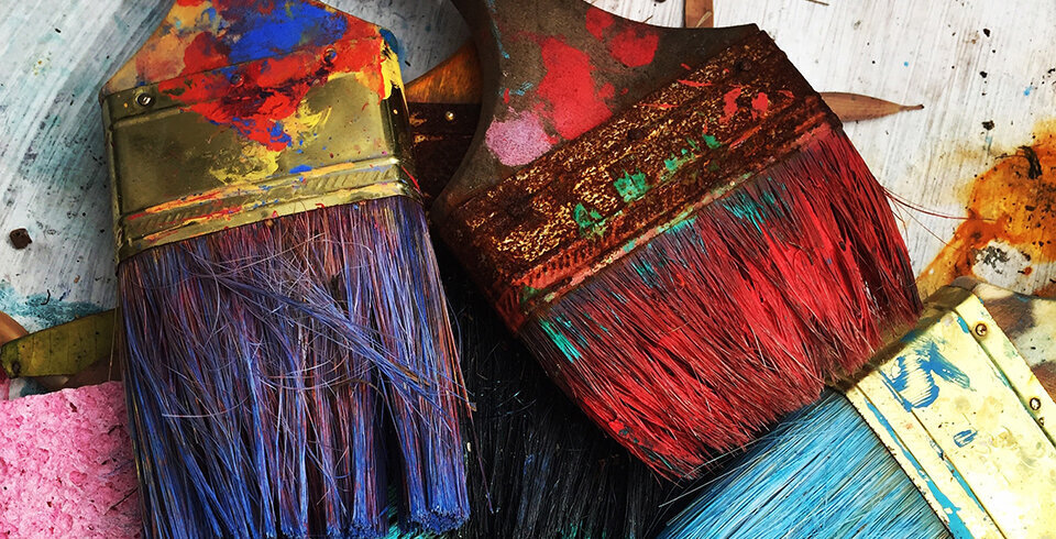 Three paint brushes with purple, red and blue paint.