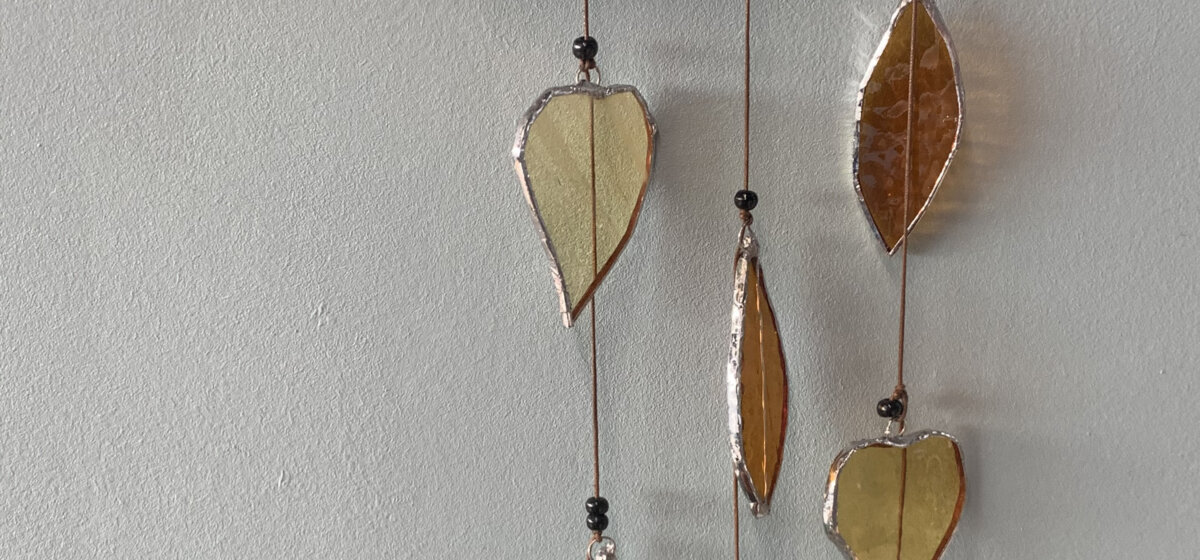A closeup of a wall hanging. Some petal-like shapes have been made from glass and are displayed on three strands of thread, with bead detailing.