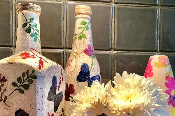 Two bottles and a vase have been upcycled and decorated with white tissue paper and painted with flowers and butterflies.
