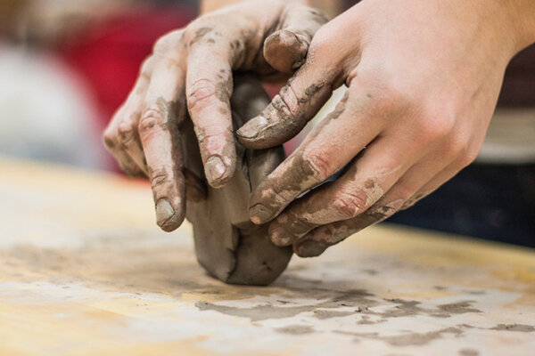 A photo of a person making clay.