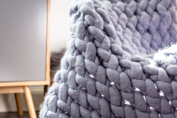 A giant grey wool throw with big knitting knots draped across a chair.