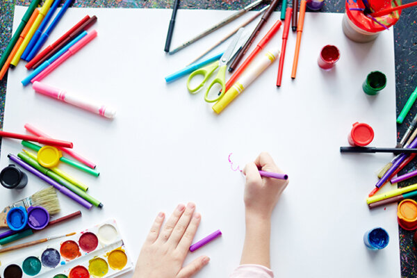 The hands of a child drawing on white paper surrounded by art materials.