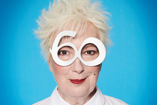 A photograph of Jenny Eclair. She is wearing large cartoonish white glasses, and the background is a light blue.