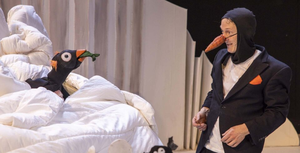A production shot of an actor dressed as a penguin looking at a penguin puppet with a fish in its mouth.