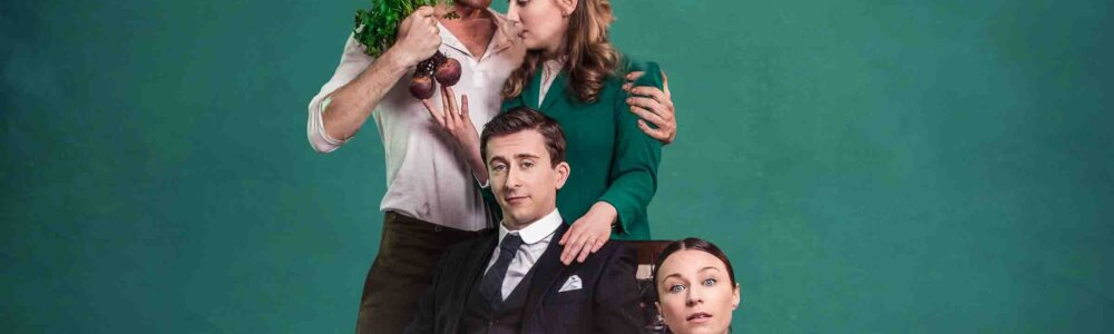 A man wearing a suit sits in a wheelchair with a blanket covering his legs. A woman dressed as a maid kneels next to him. Behind the man is a woman in a green suit. A man in a white shirt has his arm around her and holds a bunch of beetroot.