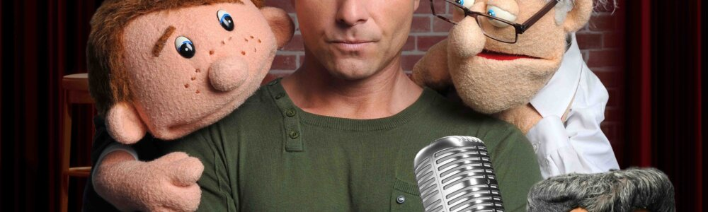 Paul Zerdin is standing centre of frame with his puppet characters around him
