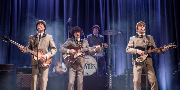 A photo of four band players in suits playing guitars.