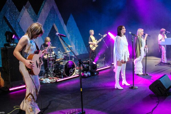 A group of singers and musicians, dressed in costumes from the 1970s so they resemble the band ABBA.