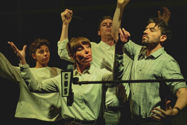 A group of two women and two men stand around a microphone with raised arms.