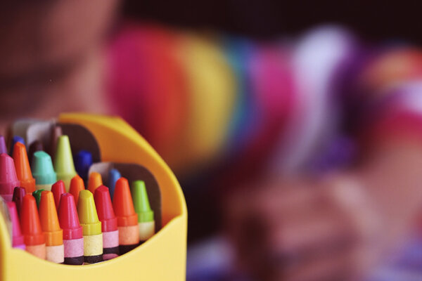 A child drawing using crayons.
