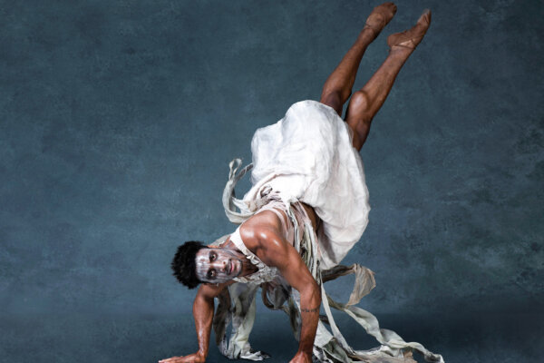 A man with white face paint is lifting himself up in the air with his hands, his legs at an angle pointing upwards. He is wearing ballet shoes and a white dress that has become disheveled, resembling rags.