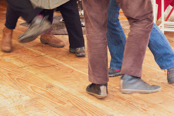 The lower legs and feet of dancing couples. wearing casual clothes and shoes.