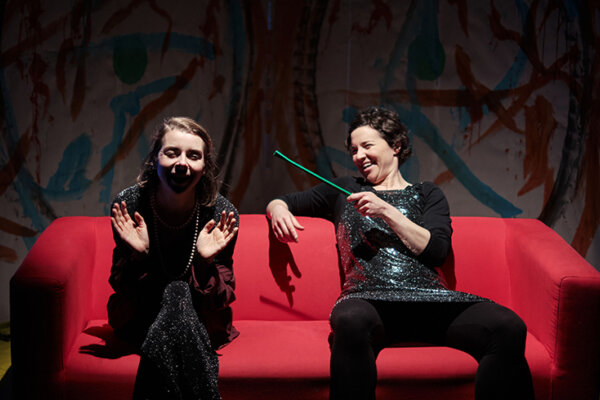 2 female actors sitting on a red sofa.