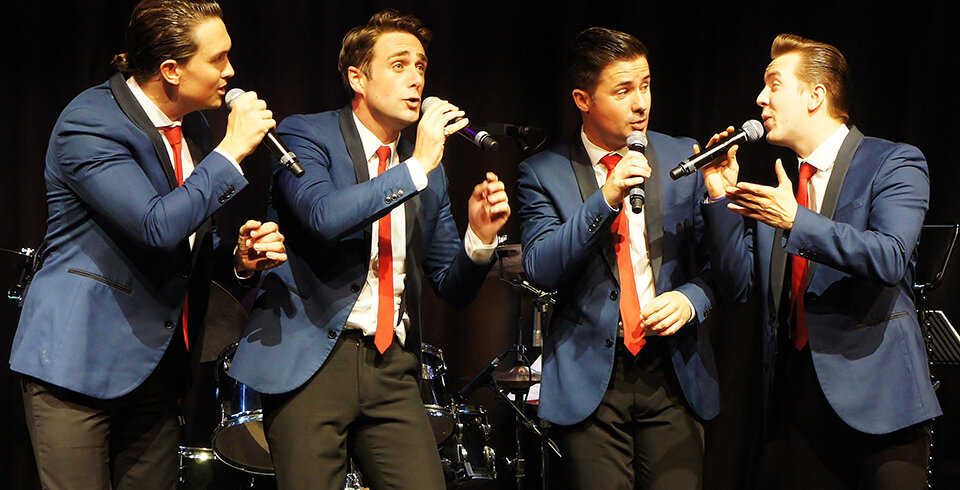 4 male singers in blue suits.