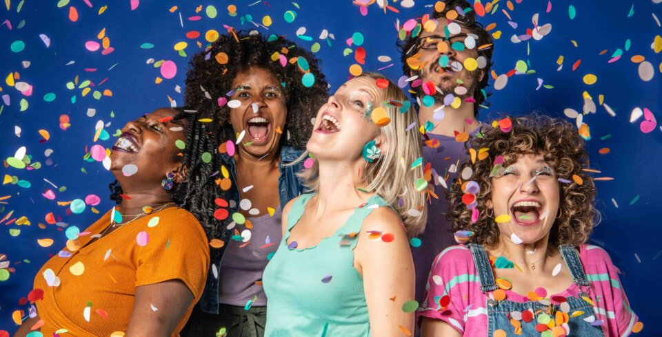 Four women and one man stand in a group. They are wearing brightly coloured t-shirts and are being showered in colourful confetti.
