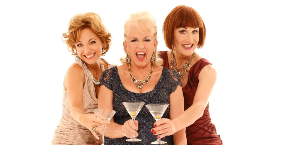Three women stand in a group holding cocktail glasses.