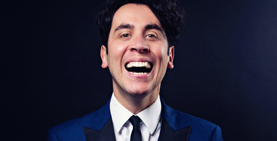 Magician Pete Firman is wearing a blue suit and is laughing at the camera.