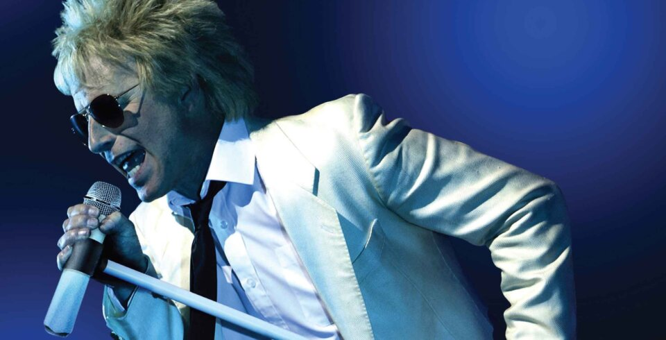 A singer dressed as Rod Stewart, singing into a microphone
