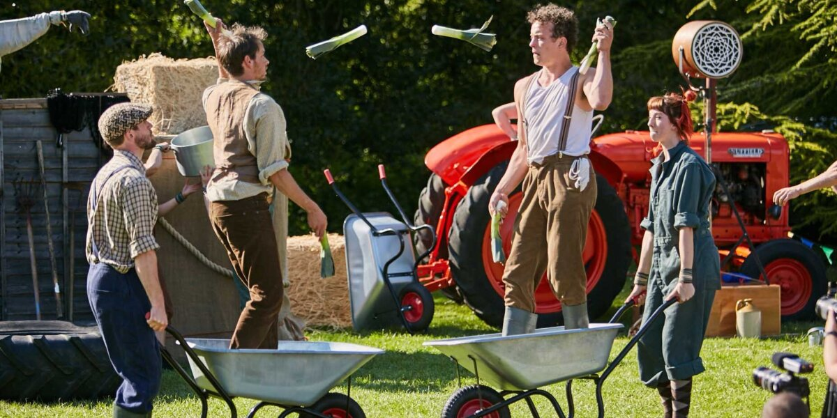 Two pairs of performers, 2 are holding wheelbarrows while two performers stand in each wheelbarrow and juggling leeks.