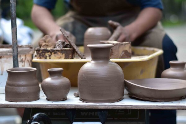 A table in the foreground with a row of freshly created clay pots and bowls. In the foreground is a potter sat at the potter's wheel.