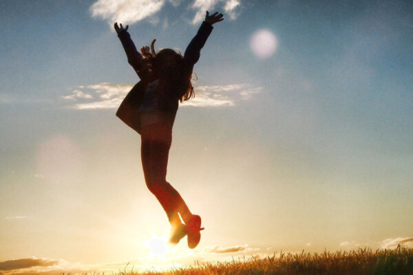 A silhouette of a young female jumping in the air with a sunset in the background