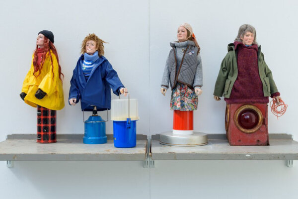 Four little models of women in colourful coats and outfits are stood on a shelf on a wall. Recycled materials have been used to make the models.