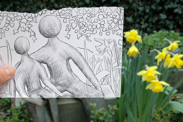 A person holds up a drawing that has been sketched of two people on a bench. The photo has been taken in a garden or park and behind the drawing is some greenery and daffodils.