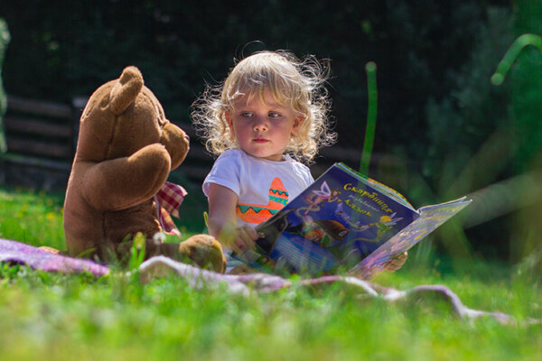 A photo of a baby sitting outside with a brown teddy bear.
