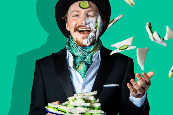 A man in a suit and top hat is holding a plate of cucumber sandwiches. He has thrown them in the air and some have landed on his face. He is laughing.
