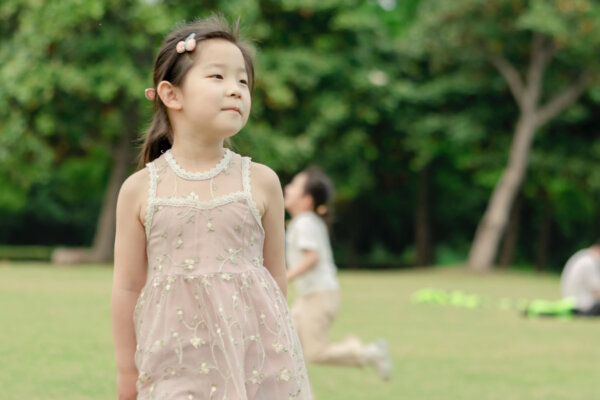 A girl with brown hair wearing a pink dress stands in a park with her arms at her side, her eyes focusing on something in the distance which is out of shot.