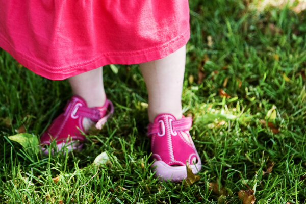 A close up of a little girl's pink trainers, who is stood on grass.