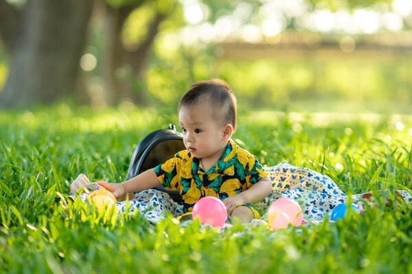 A baby with dark hair sits in a garden or park, on a blanket, playing with some multicoloured balls.