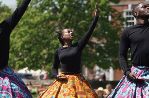 A male and female performer pose with one hand held up to the sky and the other at their hip, in a ballet-style move. They are wearing large colourful skirts and behind them is a tree.