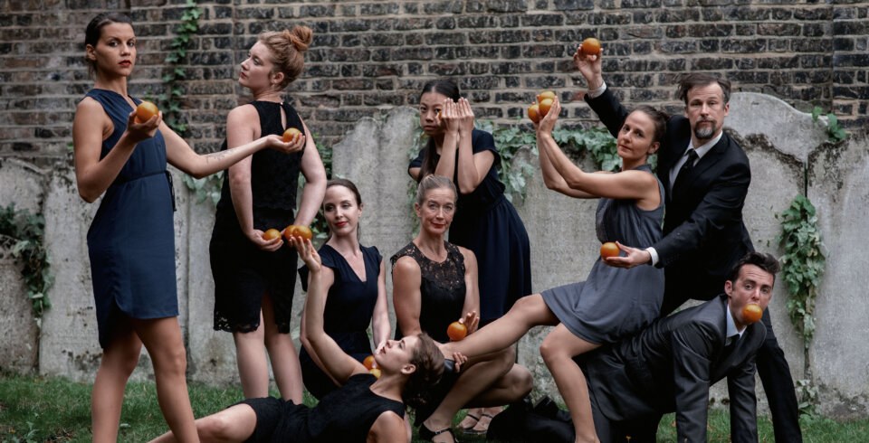 A group of 9 people, dressed in dark dresses and suits, pose at different levels, holding oranges. They are stood outside in front of a brick wall, which has ivy growing on it.