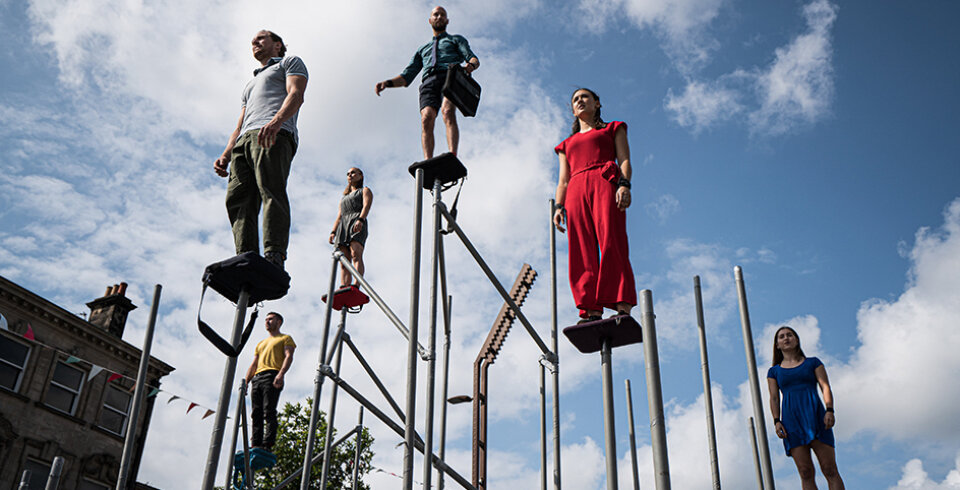 5 people standing on individual grey poles.
