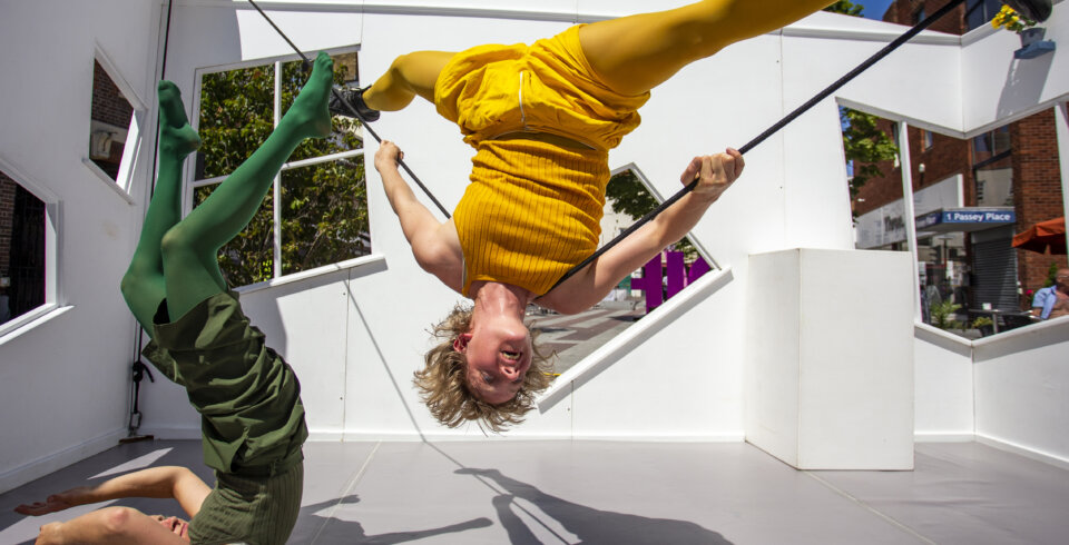 Two female circus performers, one dressed in yellow, one in green, perform inside a white house-like structure with windows. On of the performers is holding a pose on their back on the floor, whilst the other is suspended by two ropes.