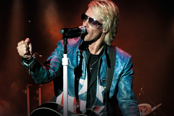 Performer dressed in an America themed jacket with long blonde hair and glasses singing into a microphone and holding a guitar.