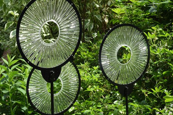 Three glass circular sculptures in a garden.