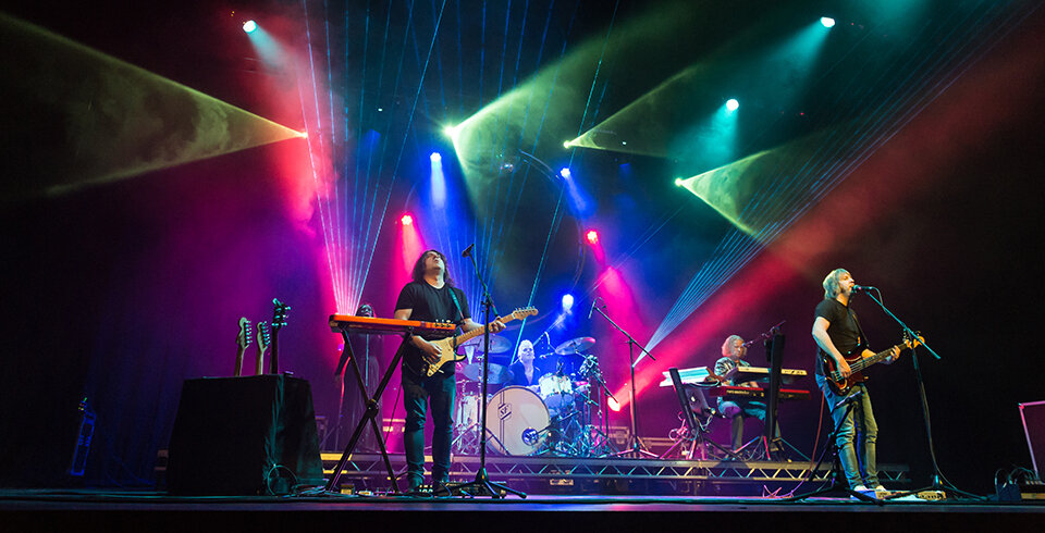 A four piece male band (two guitarists, keyboard player and drummer) are on stage, lit by green, red and blue lights.