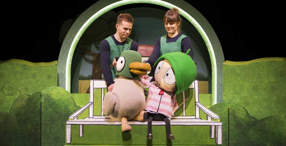 Production image featuring two performers holding Sarah and Duck puppets.