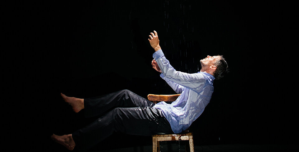 A man sitting on a seat looking upto the sky with a black background.
