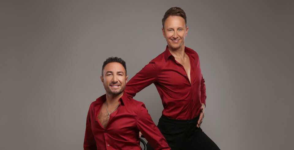 Vincent Simon (left) and Ian Waite (right) stand in the centre of the frame, facing the camera, wearing red satin shirts and black trousers.